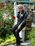 Christine, dressed in leather jacket relaxing in flower garden