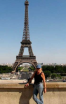 Christine in blue baseball cap, black T and jeans, in front of the Eiffel Tower