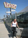 Christine in white T, black jeans, sunglasses and boots, stands in front of Pann's restaurant, Hollywood