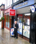 Christine, dressed for rain, stands in front of the Sunninghill news, England