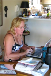 Christine in black and white bathing suit, typing on her computer